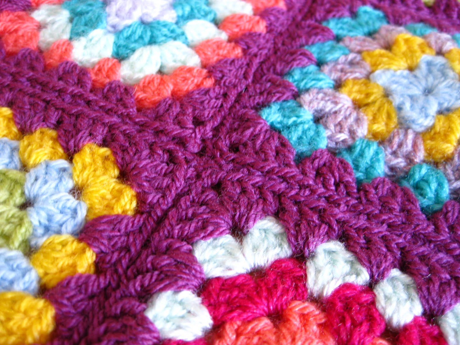 sewing granny squares to her